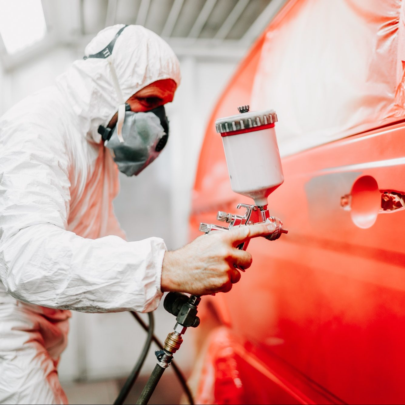 Close up details of mechanic worker, painting a red car
